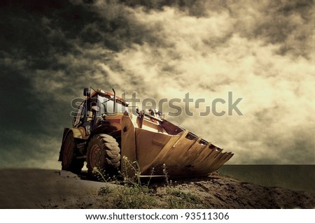 Yellow tractor on golden sunrise sky - stock photo