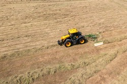 Yellow tractor towing rotary hay rake in field of cut vegetation