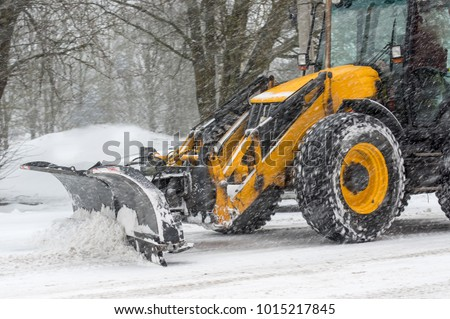 Yellow tractor with snowplow removing snow during heavy snowfall. Winter time street maintenance in hard weather conditions.