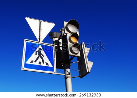 Yellow traffic light and pedestrian crossing sign