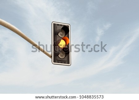 Yellow traffic light on a horizontal white metal beam, isolated on sky background - Shutterstock ID 1048835573