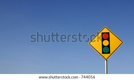 Yellow traffic sign with a stop light symbol framed against a blue sky.