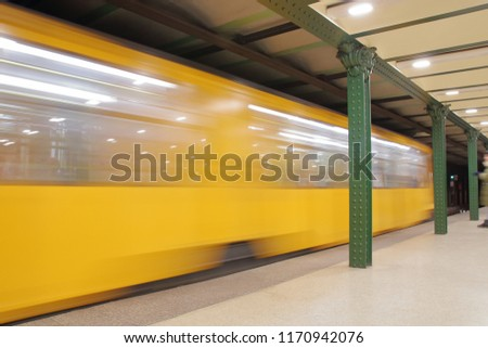 Yellow train leaving fast underground station, platform filled of artificial light, green iron pillars #1170942076