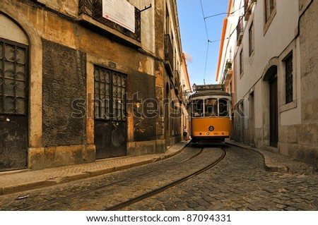 Yellow tram in Lisbon, Portugal. Small street in Alfama