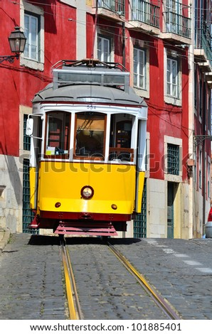 Yellow tram on narrow street, Alfama district of Lisbon. Portugal symbol