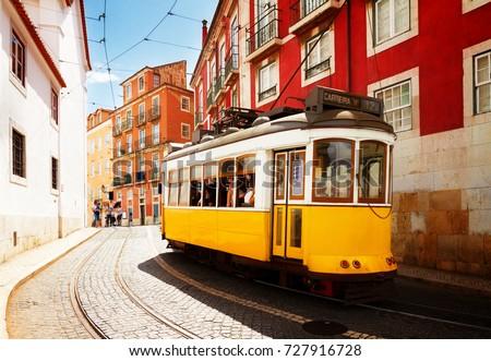 yellow tram on narrow street of Alfama district, Lisbon, Portugal, retro toned