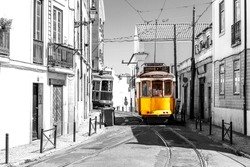 Yellow tram on old streets of Lisbon, Alfama, Portugal, popular touristic attraction and destination. Black and white picture with a coloured tram.