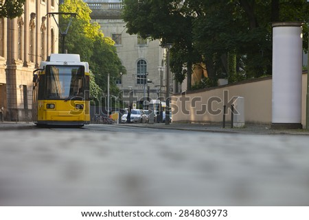 Yellow tram on the street with advertising pillar