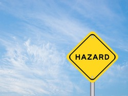 Yellow transportation sign with word hazard on blue sky background