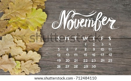 Yellow tree autumn leaves frame composition on old wooden background. Great season texture with fall mood. Nature background with hand lettering November and monthly calendar.