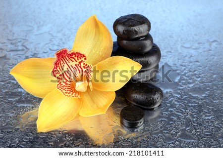 Yellow tropical orchid flower and spa stones on bright background