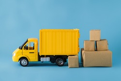Yellow truck delivery Shipping Boxes on blue background. Cargo transportation, delivery service. Transport company. Infrastructure and logistics. Unloading cardboard box.