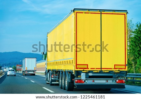 Yellow Truck on the alphalt road of Poland. Lorry transport delivering some freight cargo. #1225461181