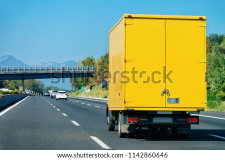 Yellow truck on the road in Italy. Lorry transport delivering some freight cargo. #1142860646