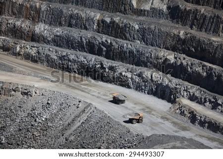 Yellow trucks inside an open cast mine in New South Wales, Australia. Barrick Cowal Gold Mine.