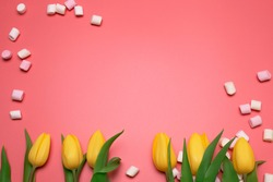 Yellow tulips and marshmallows on the pink background, with free space for text.
