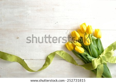 Yellow tulips bouquet with yellow green ribbon.Image of spring season
