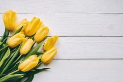 Yellow tulips bunch on white wooden planks rustic barn rural table background. Empty space for lettering, text, letters, inscription. Beautiful horizontal flat lay postcard template.