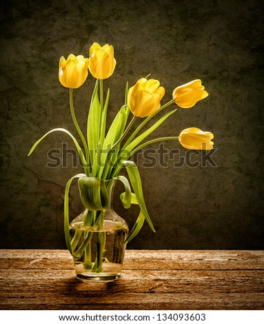 Yellow tulips in glass vase with rustic wood background