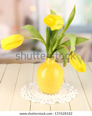 Yellow tulips in vase on wooden table on room background