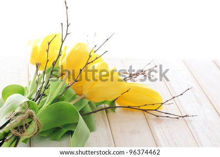 Yellow tulips with silver-bud willow on wooden table. - stock photo