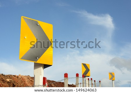Yellow turn right sign with the blue sky