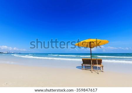 Yellow umbrella and wooden chairs on Hua Hin beach, Thailand