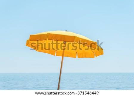 yellow umbrella near sea under blue sky #371546449