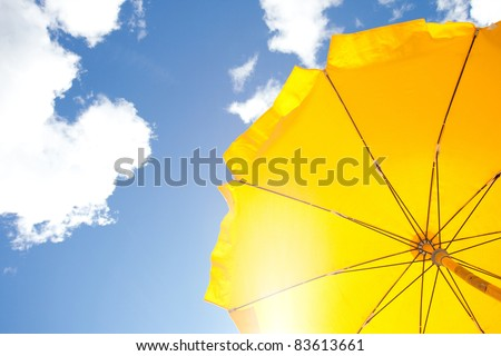 yellow umbrella on blue sky with clouds