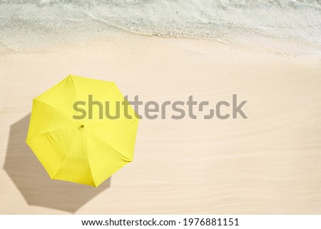 Yellow umbrella on tropical sand beach. Top and aerial view. Ocean coastline. Drone photo. Background