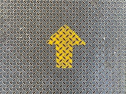 yellow up direction arrow sign on old weathered metal plate surface texture wall background.