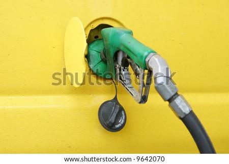 Yellow van being fueled with diesel
