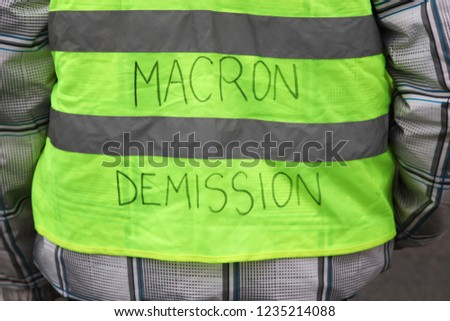 Yellow vests protest against higher fuel prices in France and text on the yellow vest president Macron departure in French
