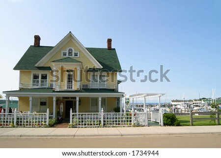 Yellow victorian style house with green roof blue sky and - Yellow house with green roof ...