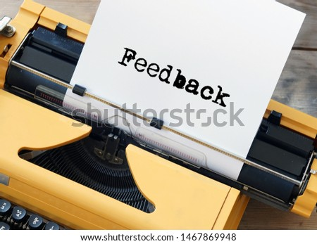 Yellow vintage typewriter with the word Feedback typed on a sheet of paper