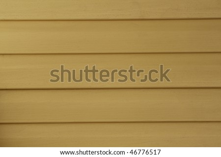 Yellow vinyl siding on a house; good for background