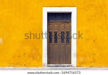 Yellow wall facade and door in the city center of Izamal, Yucatan Peninsula, Mexico.