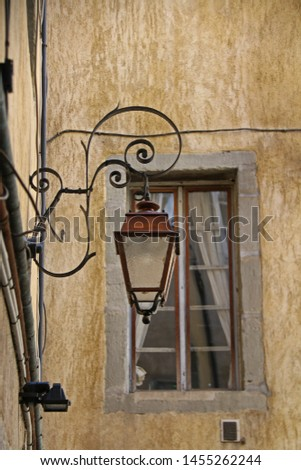Yellow wall of old house in narrow lane. Lantern and window. Chambery France