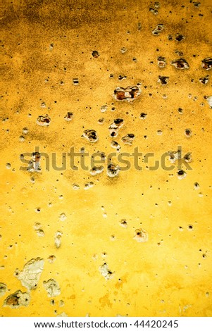 Yellow wall with bullet holes