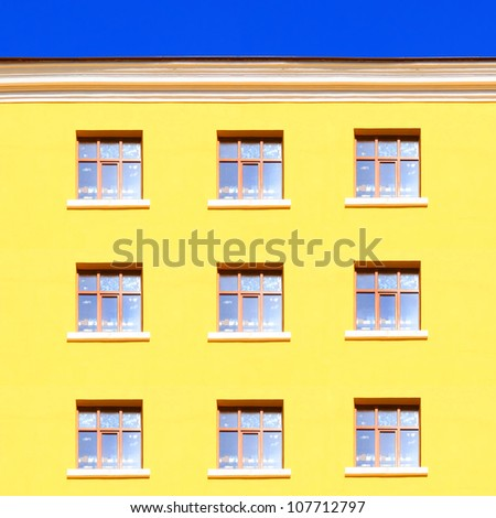 Yellow wall with windows and blue sky