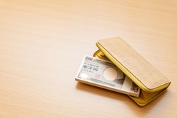 Yellow wallet and a wad of 10,000 yen. Translation on bill text: