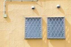 Yellow walls with plumbing and two lattice windows