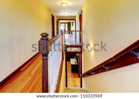 Yellow walls with stairway, hardwood floor and wood railing.