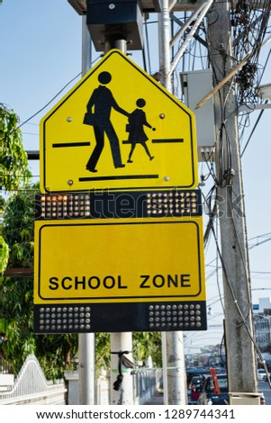 Yellow warning school zone sign with many dots of light.