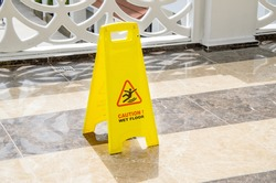 Yellow warning sign Caution Wet Floor on a marble floor in a public area. Preventing injuries to hotel guests during wet cleaning of halls and public places.