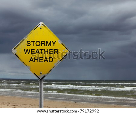 yellow warning sign of bad weather ahead against stormy sky