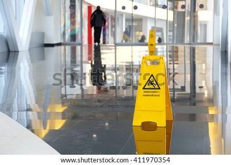 Yellow warning sign wet floor in Russian language #411970354