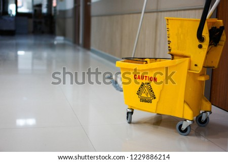 Yellow water tank for floor cleaning and write a dangerous warning message to people such as caution or attention on cleaning tank. Hospital cleanliness is important.