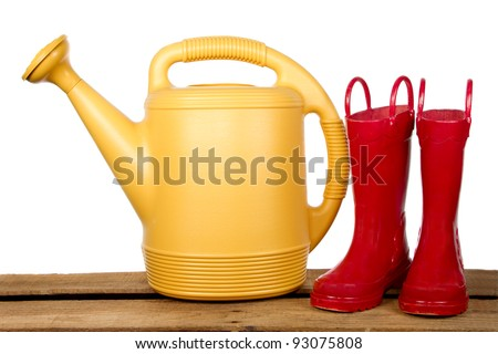 Yellow watering can and red boots on a wooden plank