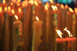 yellow wax chinese candles with lucky symbol burning red Chinese candle in chinese temple or shrine. write in Chinese mean good luck and lucky symbol